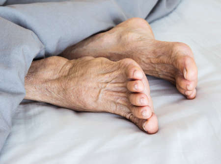 Old feet on the bed Stock Photo