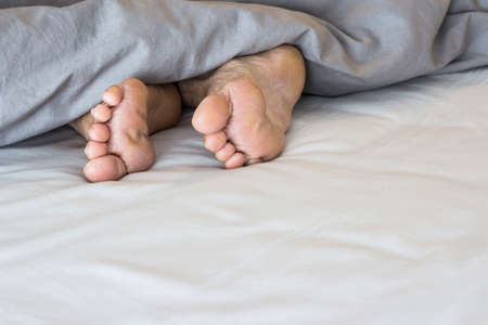 sere: Old feet on the bed Stock Photo