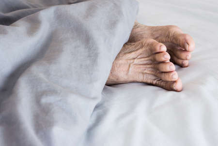 shrunken: Old feet on the bed Stock Photo