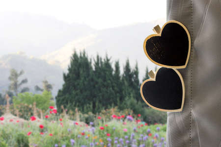 design objects: Love concepts of wooden heart clothespin on the curtain with flowers garden view