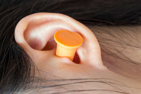 disturbance: Young woman with earplugs sleeping on the bed Stock Photo