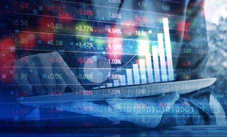 デジタル タブレットの株価グラフをチェックしている女性実業家 写真素材