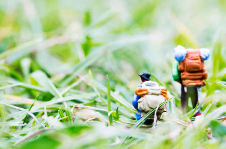 backpackers: Miniature backpackers walking on the grass Stock Photo