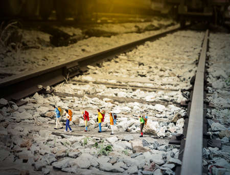 backpackers: Travel concept of miniature backpackers walking on the railway Stock Photo