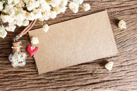 Blanco papier label en droge bloemen op houten achtergrond