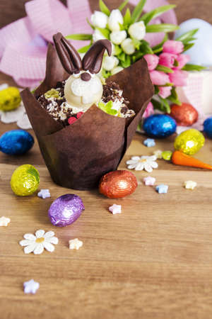 sunday: Easter cupcake and chocolate eggs on wooden background Stock Photo