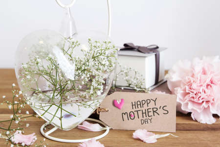 Gypsophila flowers in heart bottle with happy mothers day on paper tag on wooden table