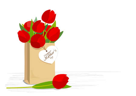 brown paper bag: Red tulips in brown paper bag with mothers day card on wooden floor