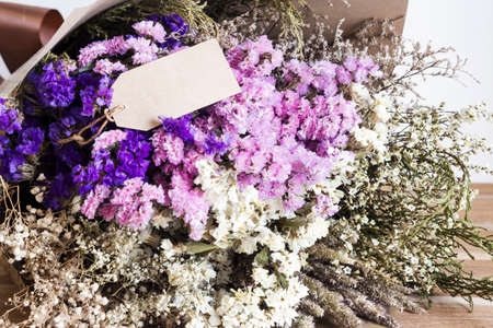 aniversary: Bouquet of dried flowers with blank paper tag on the wooden table