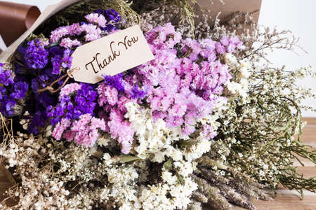 aniversary: Bouquet of dried flowers with thank you card on the wooden table