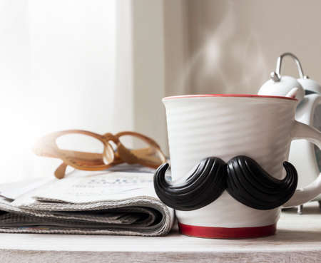 Cup with mustache on wooden table for fathers day concept 免版税图像