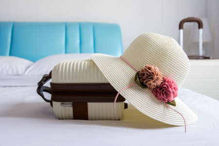 portmanteau: Hat and luggage on bed in the bedroom Stock Photo