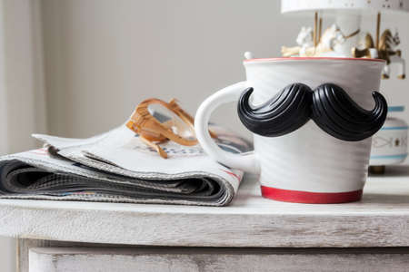 caballo bebe: Cup with mustache on vintage cabinet for fathers day concept