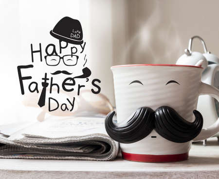 Cup with mustache on wooden table for fathers day concept Standard-Bild