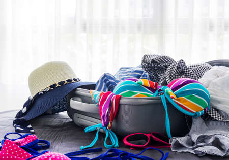 bed clothes: Colorful bikini and clothes in luggage on the bed