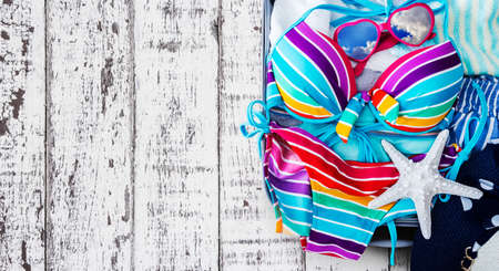 portmanteau: Colorful bikini and clothes in luggage on the wooden background