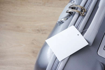 portmanteau: Suitcase with blank tag label on wooden floor