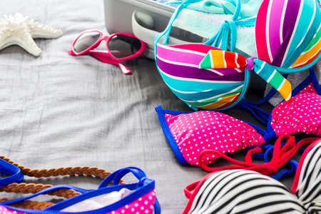 two piece swimsuits: Bikinis and clothes in luggage on the bed