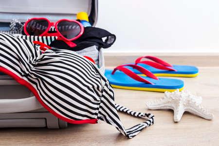 portmanteau: Bikini and clothes in luggage on the laminate floor