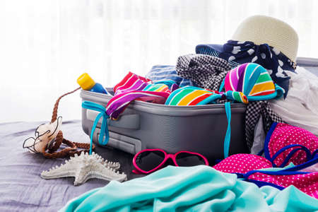 two piece swimsuits: Colorful bikini and clothes in luggage on the bed