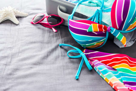 piece of luggage: Colorful bikini on the bed