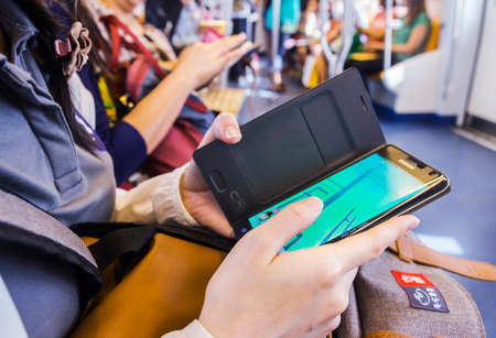BANGKOK, THAILAND - September 3, 2016: Young woman playing Pokemon Go game on sky train. Pokemon Go is a free-to-play, location-based augmented reality game developed by Niantic.