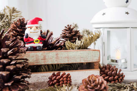 lamplight: Christmas decoration of santa claus and pine cones on wooden cabinet