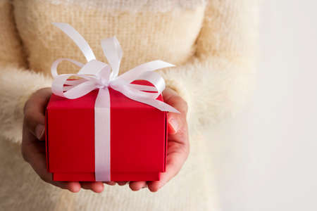 december 25: Young woman hands holding red gift box  Stock Photo