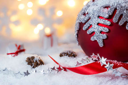 Red christmas ball with snowflake on the snow and bokeh light