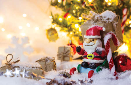 Christmas decoration santa claus and gift box on the snow with bokeh light Stock Photo