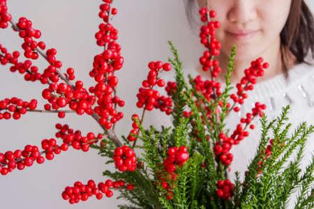 Cute woman holding ilex verticillata or winterberry for christmas decoration Stock Photo