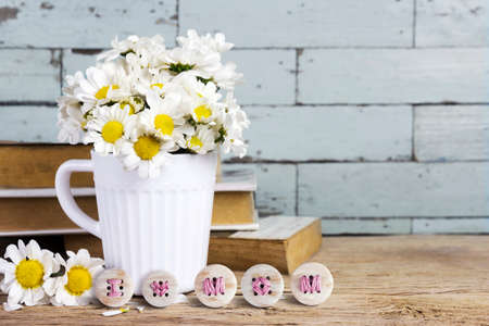 bottons: Mothers day concepts of daisy flowers in white cup with i love mom embroidery on wooden bottons