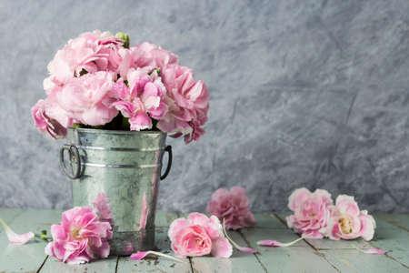 Pink carnation flowers in zinc bucket on old wood Standard-Bild