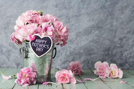 Roze anjerbloemen in zinkemmer met de gelukkige dagbrief van moeders op houten hart Stockfoto