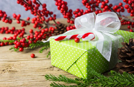 Christmas decoration of green gift box and red winterberry on old wood