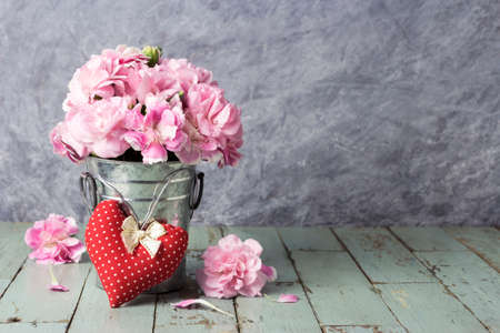 Red heart and pink carnation flowers in zinc bucket on old wood Stock Photo