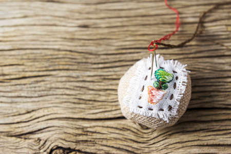 Pin cushion on old wood table Stock Photo