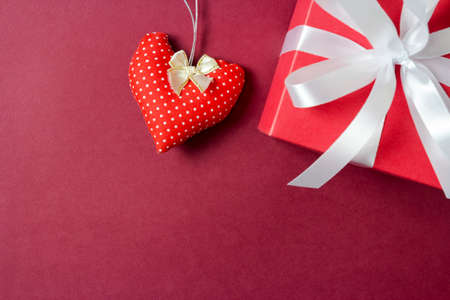 Red fabric heart and gift box on paper background
