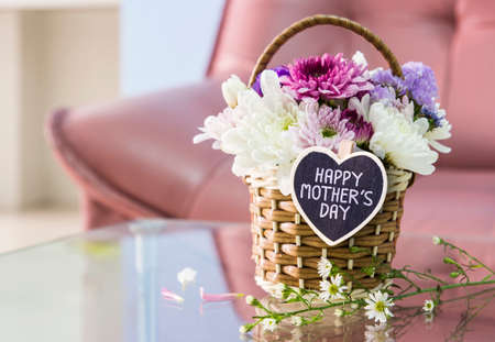 Happy mothers day letter on wood heart and chrysanthemum flower in the basket