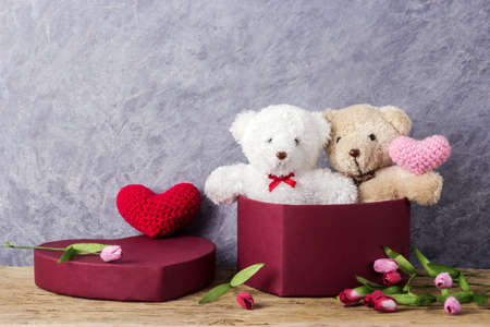 swain: Love and valentines day concept of teddy bear in red heart gift box on wood table