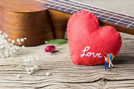 tercet: Love concept of miniature couple backpacker and ukulele with red heart on old wood Stock Photo