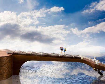 Love and travel concept of miniature couple backpacker walking on ukulele bridge at river Stock Photo