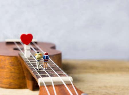 Love concept of miniature couple walking on ukulele