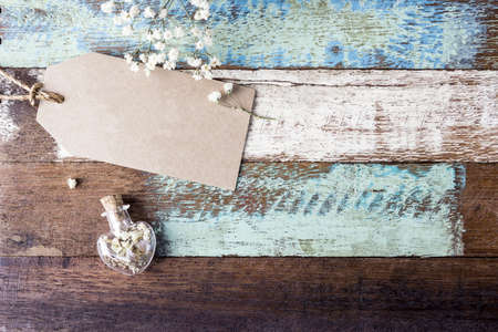 Love concept of blank brown paper tag and gypsophila flowers in heart bottle on vintage wood
