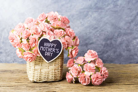 Happy mothers day concept of Paper carnation in weave basket on old wood with copy space  Stock Photo