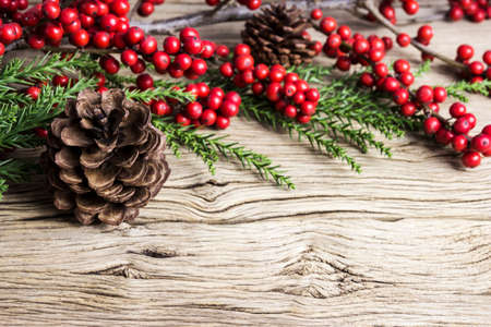 Christmas decoration of pine cone and red winterberry on old wood