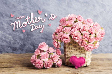 Happy mothers day concept of pink paper carnation flowers in weave basket with red heart on old wood