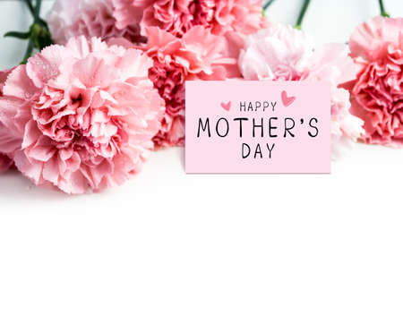 Happy mothers day message on paper and pink carnation flower on white background