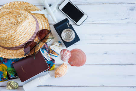 Overhead view of Hipster Traveler accessories and items on white wooden background ,Travel and Holiday concept.
