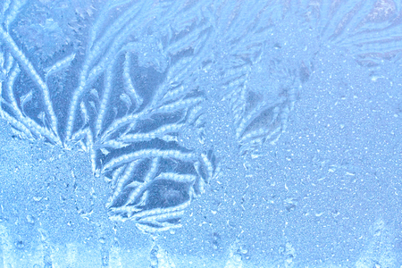 Beautiful patterns are drawn by a frost on the windows of houses